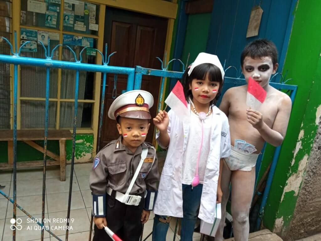 Tiga orang anak berpose dengan gaya berbeda sebelum karnaval